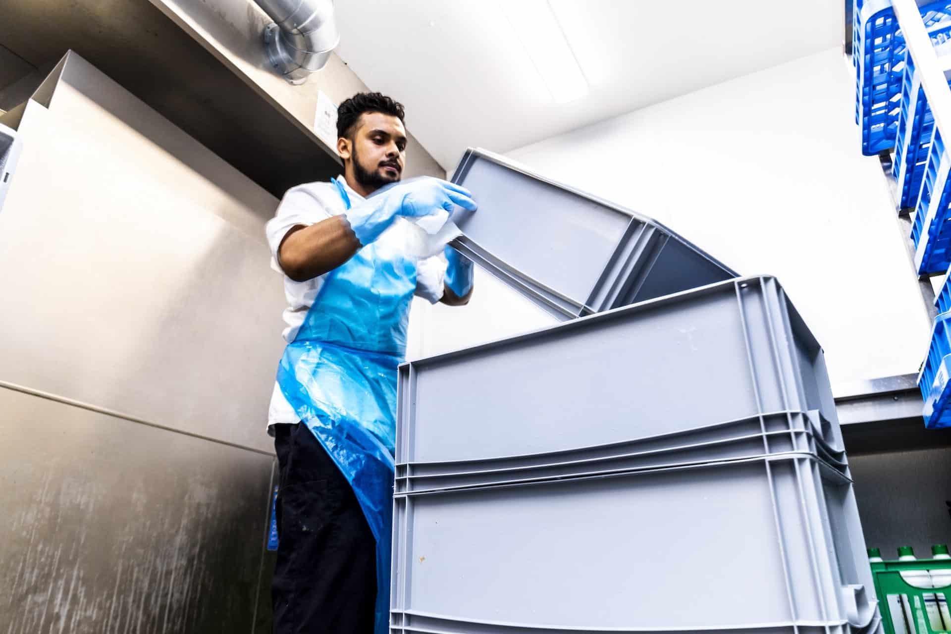 Køkken medarbejder hjælper med at rydde op
