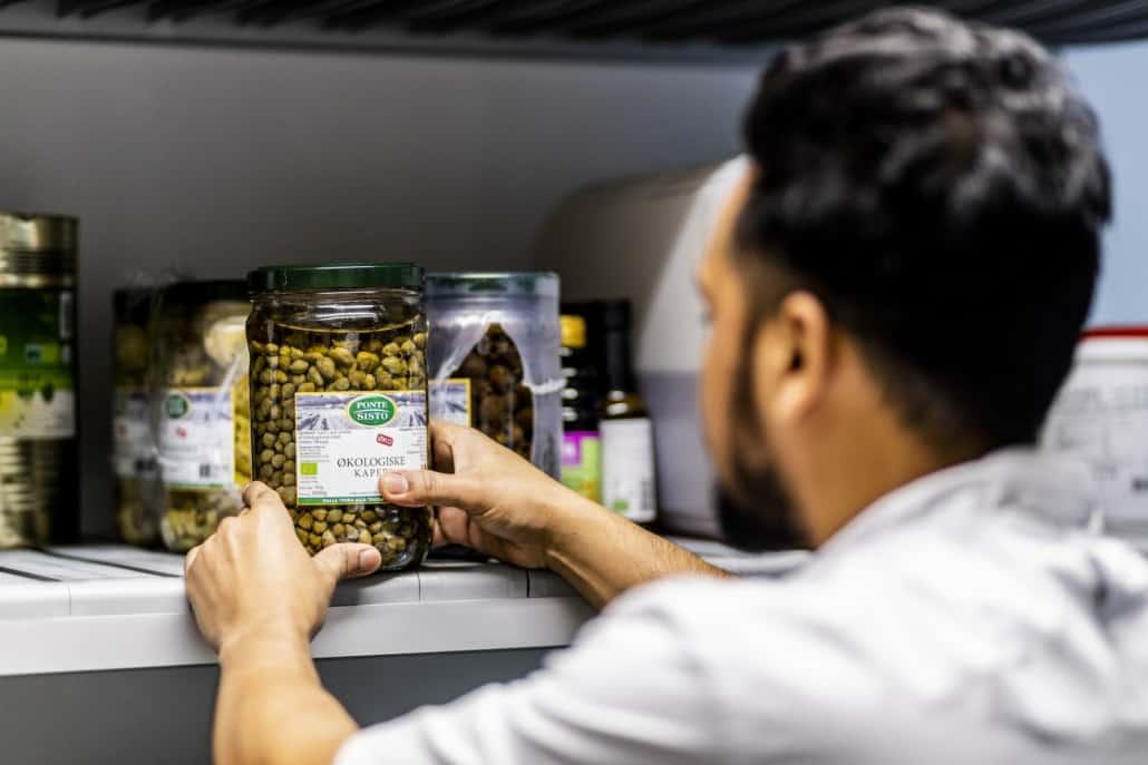 Vikar pakker hylde med madvarer